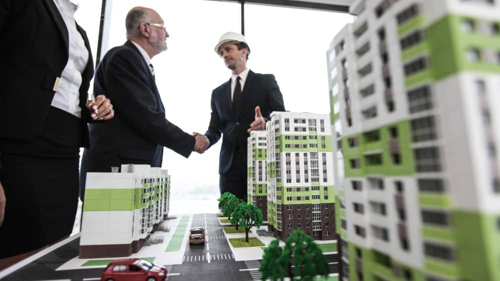 Business people standing near houses models